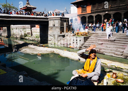 Pashupatinath Temple, Kathmandu Valley, Bagmati, Nepal, South Asia : A brahman sits by the Bagmati river where cremations are taking place at  Pashupa - Stock Photo