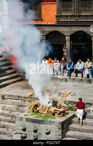 Pashupatinath Temple, Kathmandu Valley, Bagmati, Nepal, South Asia : People attend to a cremation funeral by the river Bagmati at Pashupatinath temple - Stock Photo