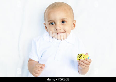 Portrait of cute adorable smiling laughing little indian mixed race south asian  infant boy in white shirt on white background playing with car toy - Stock Photo