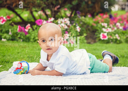 Portrait of cute adorable little indian South Asian or Middle Eastern infant boy in white shirt laying on ground with toys in park outside on bright s