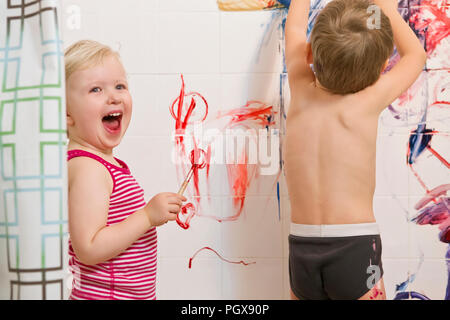 Portrait of two cute adorable white Caucasian little boy and girl playing painting on walls  in bathroom, having fun, lifestyle active childhood conce