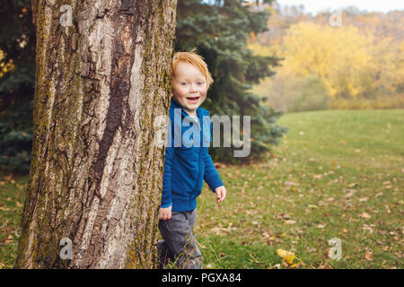 Portrait of cute adorable little red-haired smiling Caucasian boy child playing in autumn fall park outside in park