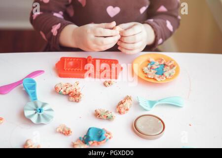 Closeup of child girl hads fingers. Kid playing plasticine playdough indoors at home. Early creativity brain development concept. Children activity. F - Stock Photo