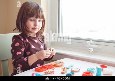 Portrait of cute white Caucasian preschooler girl playing plasticine playdough indoors at home. Early creativity brain development concept. Children a - Stock Photo