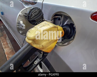 Fuel nozzles adding gasoline fuel in car at a pump gas station. - Stock Photo