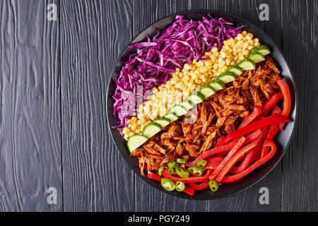 pulled pork rancho salad with thinly sliced red cabbage, corn, bell pepper, cucumber and chopped jalapeno on a black plate on a black table, view from - Stock Photo