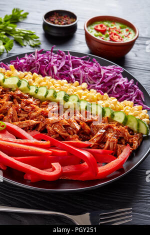 Bbq pulled pork salad with arranged rows of coleslaw, corn, sweet pepper, cucumber and jalapeno served on a black plate on a wooden table with avocado - Stock Photo
