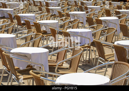 Empty sidewalk tables and chairs in a sunny summer day in Italy - Stock Photo