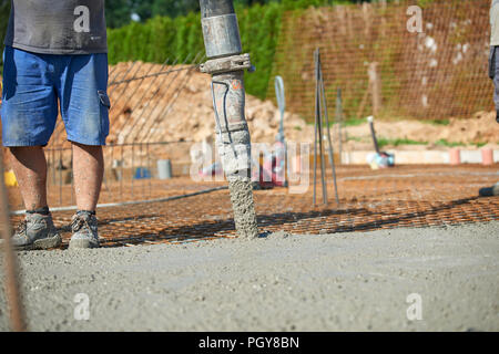 Concrete pouring during commercial concreting floors of building - Stock Photo