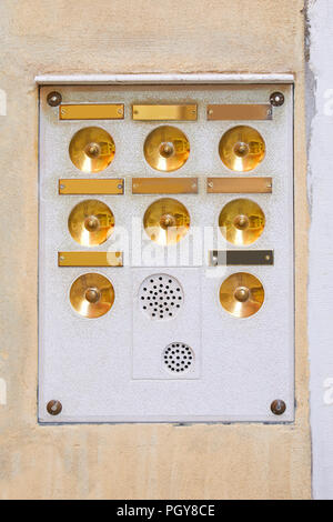 Ancient intercom in Venice with golden buttons and blank plates - Stock Photo