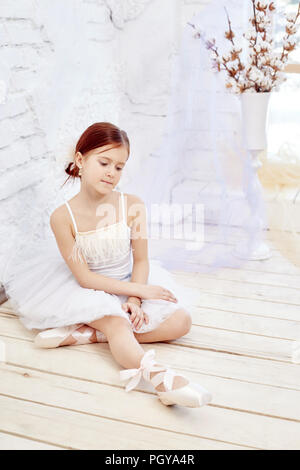 Little prima ballet. Young ballerina girl is preparing for a ballet performance. Girl in a white ball gown and Pointe near the window, beautiful red h - Stock Photo