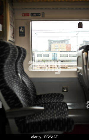 Two empty airline style seats on an Abellio Greater Anglia train,while on a platform - Stock Photo