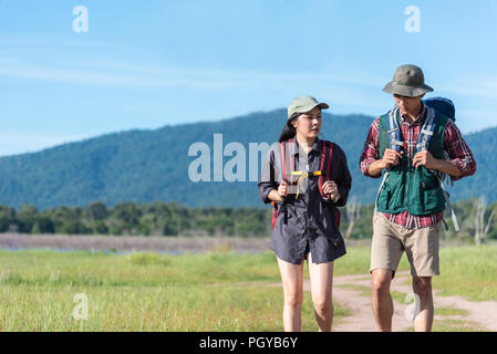 Two people walking on path in meadow field. Male and female traveler looking at attraction view point. Couples adventure at outdoors together. People  - Stock Photo
