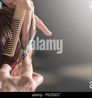 Hairdresser cutting hair of customer at salon. - Stock Photo