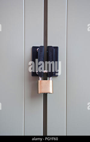 A brass security lock on a metal garden shed - Stock Photo
