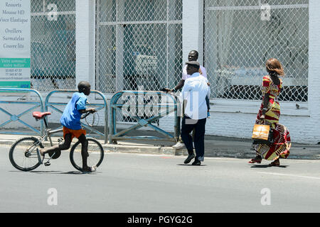 DAKAR, SENEGAL - APR 23, 2017: Unidentified Senegalese little boy pulls a bicycle along the road in Dakar, the capital and main city of Senegal - Stock Photo