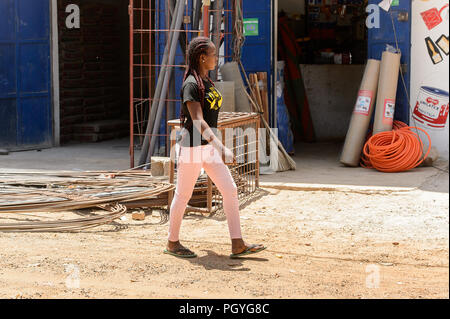 ROAD TO LAMPOUL, SENEGAL - APR 23, 2017: Unidentified Senegalese woman with braids in pink pants and black shirt walks near the mounting. Still many p - Stock Photo