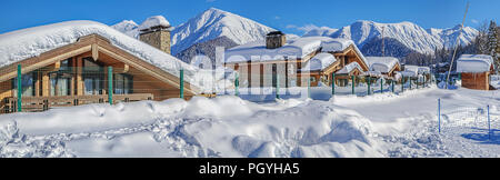 RED GLADE, SOCHI, RUSSIA - JANUARY 31, 2016: Snow-covered cottages against the backdrop of the mountains. Mountain resort 'Laura, GAZPROM' - Stock Photo