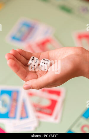 The hand throws game dice on the background of the playing field. vertical photo. - Stock Photo