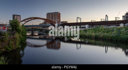The River Irwell flows between Manchester and Salford under the newly constructed Ordsall Chord railway, part of the 'Northern Powerhouse' investment  - Stock Photo
