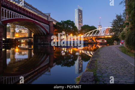 Manchester, England, UK - June 30, 2018: Houseboats light up in Castlefield Basin as dusk falls on Manchester City Centre, with a Metrolink tram passi - Stock Photo