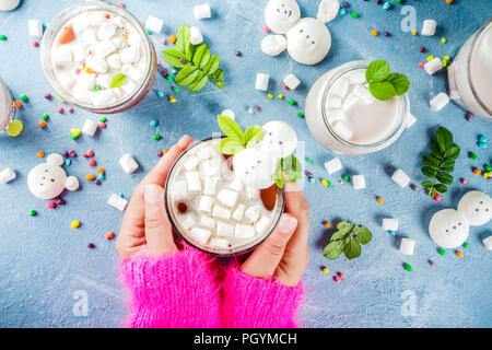 Girl drinks hot chocolate with funny marshmallow in form snowmen, white bears, with sweets and decorative leaves, light blue background, top view copy - Stock Photo