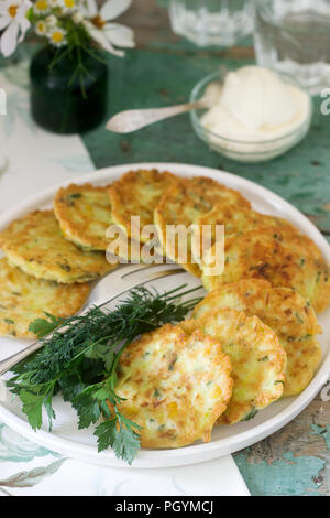 Pancakes with zucchini and sweet corn, served with sour cream, parsley and dill. Vegetarian food. - Stock Photo