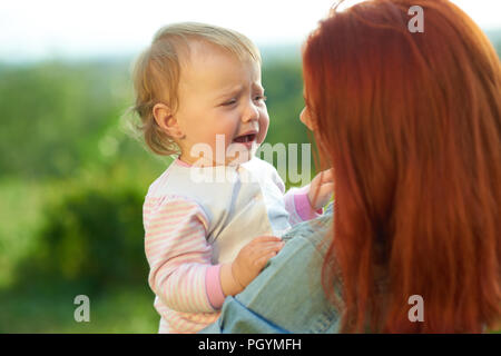Crying daughter sitting on mother's hands during sunny day in the field. Young mom trying to calm down little baby, talking to her. Woman having red h - Stock Photo