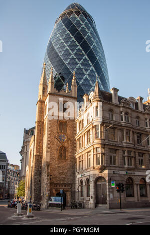 London, England, UK - July 3, 2009: Old and new are juxtaposed in the city of London with St Andrew Undershaft, a traditional parish church, standing  - Stock Photo