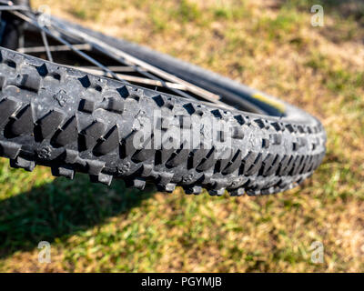close up of dirty mountain bike wheel profile with dirt and natrual background - Stock Photo