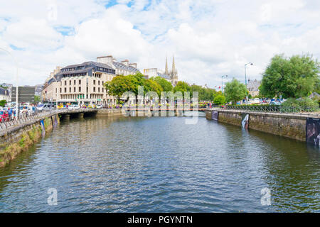 Quimper, France - August 8 2018: Looking down the Odet River as it flows through Quimper, people walk on tree lined banks, bordered by commercial buil - Stock Photo