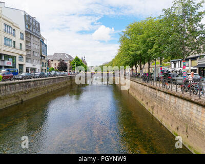 Quimper, France - August 8 2018: Looking down the Odet River flowing through Quimper between tree lined banks, bordered by commercial buildings and pa - Stock Photo