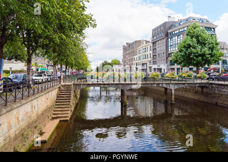 Quimper, France - August 8 2018: Looking down the Odet River flowing through Quimper, people walk on tree lined banks, bordered by commercial building - Stock Photo