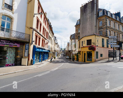 Morlaix, France - August 10 2018: A quite day on the Rue de Paris in Morlaix. A lady with a walking stick makes her way across the road. - Stock Photo