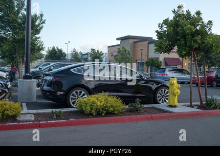 Black Tesla Model 3 electric car from Tesla Motors parked in a parking lot at a shopping mall in Dublin, California, May 21, 2018. () - Stock Photo