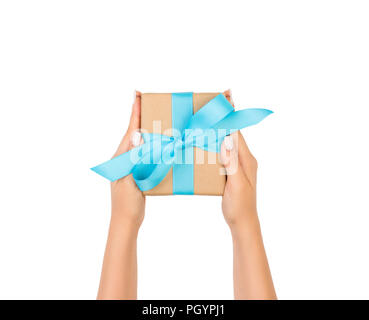 woman hands holding gift wrapped and decorated with blue bow isolated on white. - Stock Photo