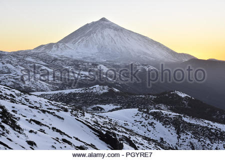 Pico del Teide at dusk - 3718 m high mountain and volcanic landscape of Teide National Park covered with snow. Tenerife Canary Islands Spain. - Stock Photo