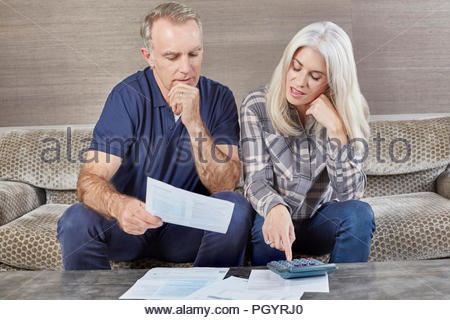 Mature married couple working from home together. - Stock Photo