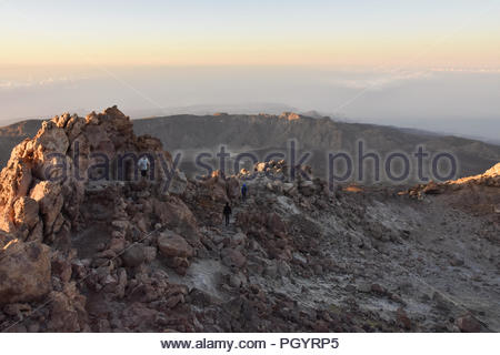 Volcanic landscape of Teide National Park Tenerife Canary Islands Spain. Hikers descending from Mount Teide summit (3718 m) in the morning. - Stock Photo