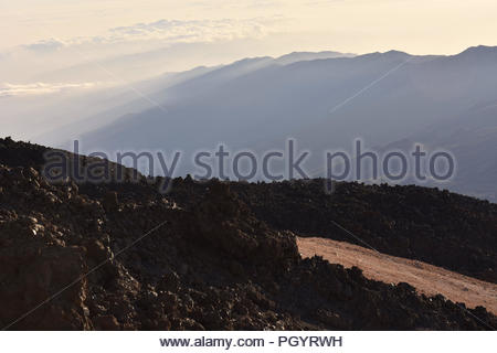 Old lava flow - morning light penetrates into volcanic valley of Teide National Park Tenerife Canary Islands Spain. Elevated view from Mount Teide. - Stock Photo
