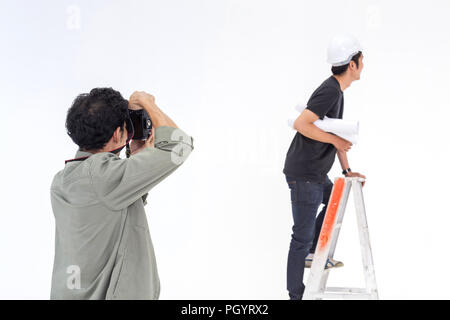 asian photographer is shooting a young man model in asian engineer concept in the studio for the stock photo. - Stock Photo