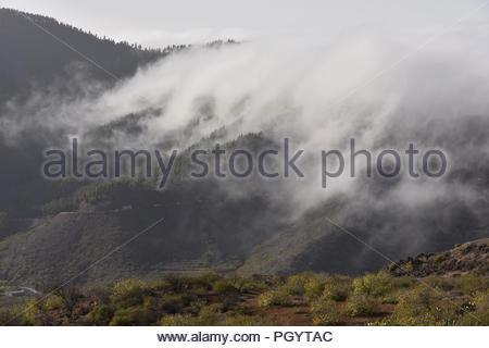 Mist forming over the mountains and descending into the valley near Santiago del Teide, northwest of Tenerife Canary Islands Spain. - Stock Photo
