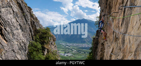 A young boy on an exposed Via Ferrata in Switzerland - Stock Photo