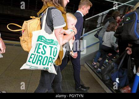 Woman with baby and carrier bag (No to Brexit) Yes to Europe sign pro European Union leaving underground train with crowd in London UK  KATHY DEWITT - Stock Photo
