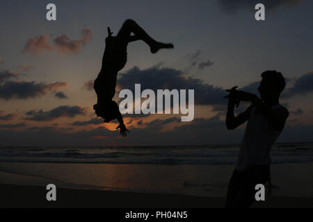 Two Palestinian youths, Fathi El Masry, 16, and Mohamed El Sakany, 15, practice the sport of parkour on the beach of Gaza City. The beach of Gaza is one of the few places of respite for the Gazan, who have lived under Israeli blockade since 2007. 28th Aug, 2018. Parkour is a physical discipline made of climbing, jumping, running, and balancing that requires the training of one's body and mind in the development of strength, agility, coordination, but also of self-discipline and determination Credit: Ahmad Hasaballah/IMAGESLIVE/ZUMA Wire/Alamy Live News - Stock Photo