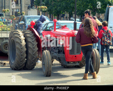 Glasgow, Scotland, UK. 29th  August, 2018. Lunchtime visitors where treated to a bit of living history as a classic  red 1964 Massey Ferguson 35X tractor appeared in the city's George Square. Locals and tourists watched on as the turf that was lifted for the recent European Championships welcoming centre was replaced. The model sports unusual double wheels to increase traction and was modified by the proud owner pictured. Gerard Ferry/Alamy news - Stock Photo