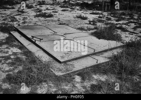 Abandoned industrial doors, left in the sand to rust - Stock Photo