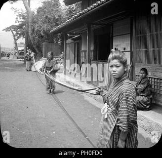 [ 1900s Japan - Women Working With Silk ] —   Two women and a girl dressed in kimono and yukata work with silk in front of a home in Kanbara in Shizuoka Prefecture. The city was was the fifteenth of the fifty-three stations of the Tokaido highway.  On March 31, 2006 Kanbara ceased to exist as it became part of Shimizu-ku of Shizuoka City.  20th century vintage glass slide - Stock Photo