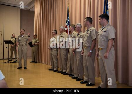 WASHINGTON (June 14, 2018) Captain Ken Collins, commanding officer of the U.S. Navy Band, introduces the Navy Band's newest Senior Chief Petty Officers, from left to right, Peter Revell, Robert Holmes, Adam Grimm, Michael Curtis, Gunnar Bruning and Michael Belinkie during a pinning ceremony in the Sail Loft on the Historic Washington Navy Yard. - Stock Photo