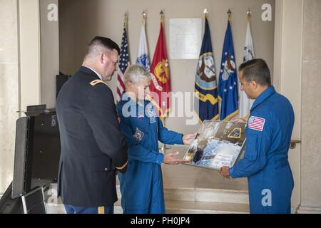 NASA astronauts Mark Vande Hei (center) and Joe Acaba (right) present Col. Jerry Farnsworth (left), chief of staff, Arlington National Cemetery and Army National Military Cemeteries, with a framed Expedition 54 patch in the Memorial Amphitheater Display Room at Arlington National Cemetery, Arlington, Virginia, June 15, 2018. The patch was flown aboard the International Space Station (ISS) during Expeditions 53/54. They also presented an ANC Employee patch to Col. Farnsworth and presented a Tomb Guard Identification Badge to Col. Jason Garkey, regimental commander, 3d U.S. Infantry Regiment (Th - Stock Photo
